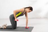 Fotografie boční pohled sportovkyně cvičení s činkami na fitness podložce