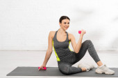 šťastný mladý sportovkyně cvičení s růžové činky na fitness mat