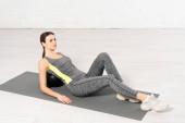 sportovkyně ve sportovním oblečení ležící na míči při cvičení na fitness podložce