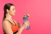 boční pohled sportovkyně držící sportovní láhev s vodou izolovanou na růžové