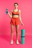 attraktive Sportlerin hält Sportflasche mit Wasser in der Hand und steht neben Fitnessmatte auf rosa