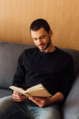pohledný a vousatý muž čtení knihy, zatímco sedí v obývacím pokoji