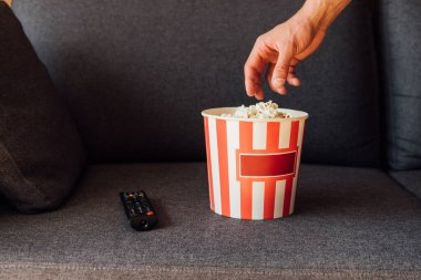 Cropped view of man reaching popcorn in bucket near remote controller on sofa stock vector