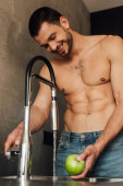 selective focus of shirtless man smiling while holding apple with faucet with pouring water in kitchen