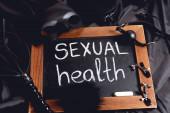 králičí maska v blízkosti tabule se sexuálním zdraví nápisy a sexuální hračky na černém hedvábí