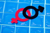 Geschlechtssymbole auf Kondomen isoliert auf blau