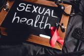 tabule se sexuálním zdravím nápisy a sexuální hračky a červená stuha na černém hedvábí