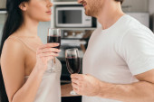 Fotografie cropped view of couple holding glasses with red wine during self isolation at home