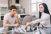 Photo beautiful couple playing chess during self isolation at home