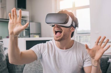Excited man using virtual reality headset at home on self isolation stock vector