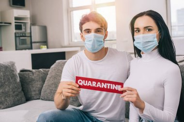 Ill couple in medical masks holding quarantine sign at home during self isolation stock vector
