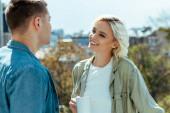 mosolygós nő kezében bögre és nézi a férfi a teraszon
