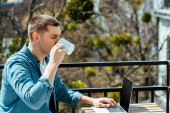 freelancer sitting on terrace with laptop and drinking tea