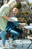 smiling business people working with laptop and papers on sunny terrace