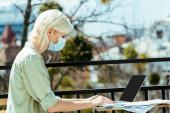 Seitenansicht der blonden Freiberuflerin in medizinischer Maske, die auf der Terrasse sitzt und Laptop benutzt