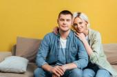 boldog fiatal pár ölelés kanapén közel sárga fal