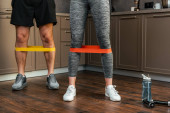 cropped view of couple exercising together with resistance bands on legs at home during quarantine