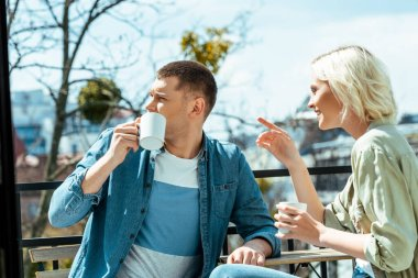 Smiling couple talking and drinking tea on terrace while woman pointing with finger away stock vector