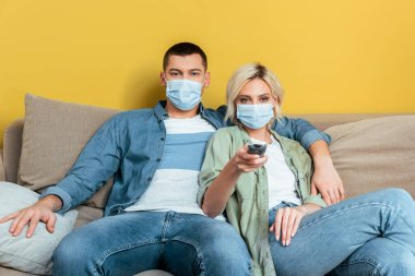 Young couple in medical masks watching tv on sofa near yellow wall stock vector