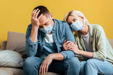 Young sad couple in medical masks on sofa near yellow wall stock vector