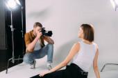 Model posiert beim Fotografieren mit Digitalkamera im Fotostudio