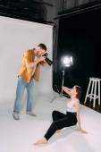 Seitenansicht eines Fotografen, der mit einem schönen Modell auf dem Boden im Fotostudio arbeitet