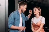 Handsome makeup artist applying mascara on beautiful young model in photo studio