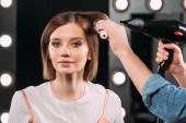 Make-up umělec dělá účes s kartáčem na vlasy a vysoušečem vlasů atraktivní žena