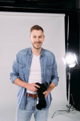 Photographer holding digital camera and smiling in photo studio