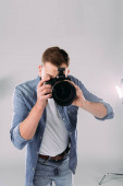 Photo Photographer taking picture with digital camera near floodlight in photo studio