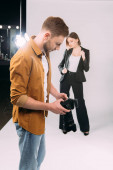 Selective focus of photographer looking at display of digital camera near elegant model and floodlight in photo studio