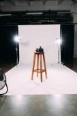 Digitální fotoaparát na dřevěné židli ve fotostudiu