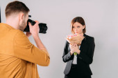 Photographer taking photo of beautiful model with bouquet of flowers in photo studio