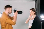 Schöne Fotografin arbeitet mit schönem jungen Model im Fotostudio