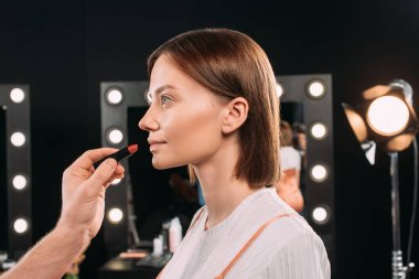 Side view of makeup artist holding red lipstick while doing makeup to beautiful model in photo studio