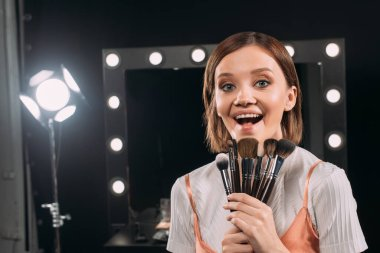 Cheerful model with cosmetic brushes looking at camera in photo studio