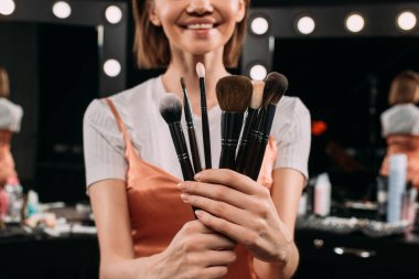 Selective focus of smiling woman holding cosmetic brushes in photo studio stock vector