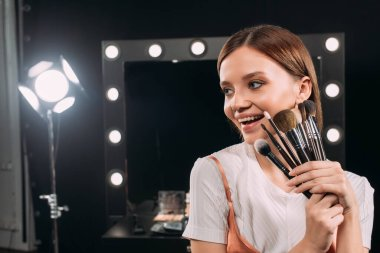 Beautiful young model smiling while holding cosmetic brushes in photo studio stock vector