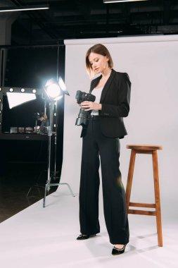 Beautiful model looking at display of digital camera in photo studio stock vector