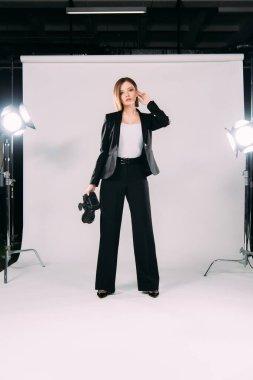 Beautiful model in formal wear holding digital camera near floodlights in photo studio
