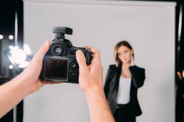 Selective focus of photographer holding digital camera near model in photo studio stock vector