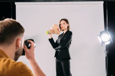 Selective focus of photographer taking photo of elegant model with bouquet in photo studio