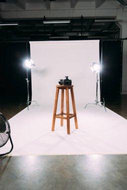 Digital camera on wooden chair in photo studio stock vector