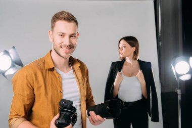 Selective focus of handsome photographer smiling while holding lens and digital camera near beautiful model in photo studio stock vector
