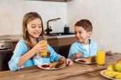 Selektiver Fokus des glücklichen Kindes mit einem Glas Orangensaft in der Nähe des Bruders und einem leckeren Frühstück
