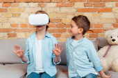 Photo happy brother looking at sister in virtual reality headset