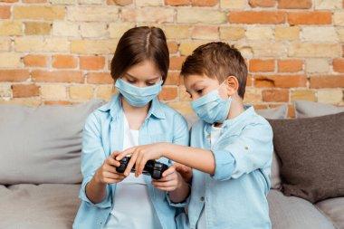 KYIV, UKRAINE - 27 Nisan 2020: evdeki joystick 'e dokunan tıbbi maskeli kardeşler