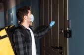Oldalnézet a szállító férfi orvosi maszk és latex kesztyű termo táska kopogtat az ajtón