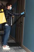 Oldalnézet a futár orvosi maszk termo hátizsák cseng a kapucsengő