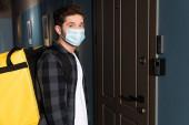 Oldalnézet futár orvosi maszk termo hátizsák nézi kamera közel ajtó bejárat